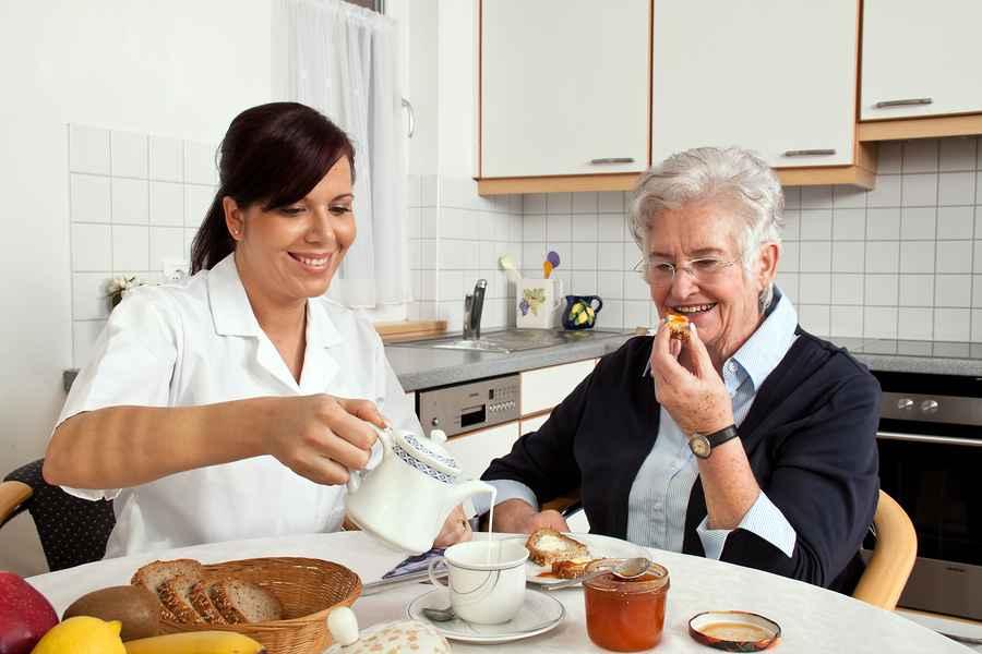 Девушка наливает чай бабушке
