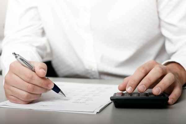 Мужчина считает на калькуляторе и пишет бумаги