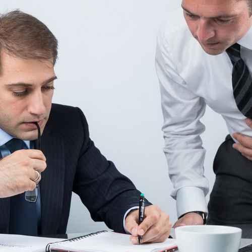 Мужчины подписывают документ
